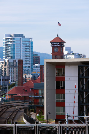 Landscape of a modern city with high multi-storey buildings modern architecture look of concrete and glass with aluminum and rails, red roofs and tower of train station with clock, sign and flag in Down Town Portland.