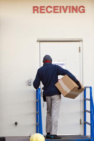 keeping: Man of the shipping service delivered the parcel cardboard box to the door of the client building with the appropriate inscription receiving. Stock Photo