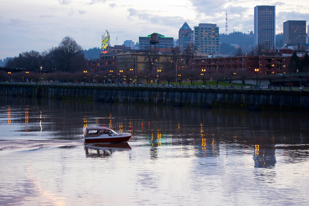 enabled: A small boat with a convertible cabin on Willamette River in the heart of Portland with an evening promenade enabled streetlights and office buildings towering above the waterfront walkways reflected lights.