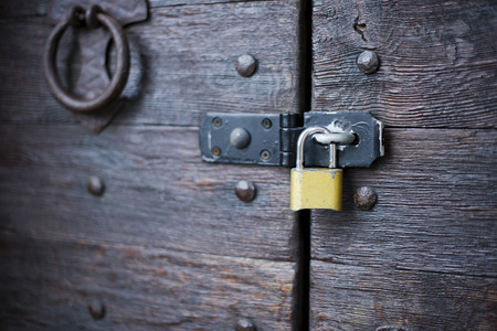 door handle: Modern yellow padlock on the metal bracket on the old wooden door lacquered in which the visible wood texture and vintage door accessories. Stock Photo