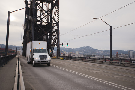 semitruck: Semi-Truck of the middle class carrying capacity white box with a booth on the road through the old iron truss lift bridge over the Willamette river on a background of Down Town Portland