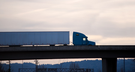 Silhouette of modern semi-truck with a high sleeper cab and a long trailer on a concrete bridge, builded on the entrance of the highway in the evening.