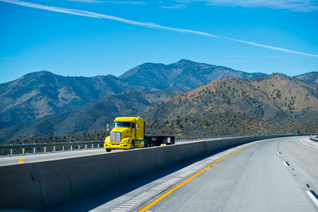 Bright yellow powerful big rig semi truck with a flat bed trailer on the interstate mountain pass highway turn with the mountain tops and blue sky.