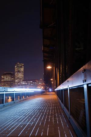 Pedestrian and bicycle path that is part of the metal transport truss bridge over the Willamette River in Portland in the twinkling night lights high-rise office buildings, cyclist headlight and some lanterns hanging on the truss bridge. photo