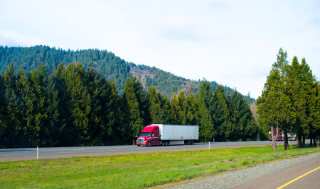 Red powerful modern professional semi truck to haul dry van trailer on the interstate highway with green dense trees supplying the road oxygen and hills forest.