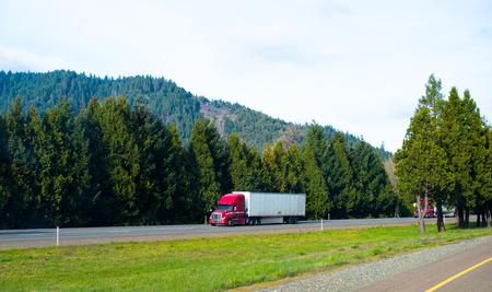 Rouge puissant moderne camion semi professionnel pour transporter sèche semi-remorque fourgon sur l'autoroute inter-États avec des arbres denses vertes fournissant la forêt de l'oxygène de la route et les collines. Banque d'images - 39689325