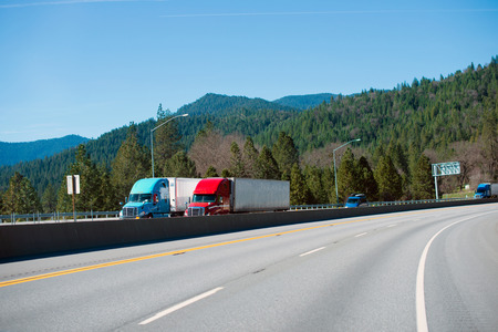 A pair of modern red and blue semi trucks with trailers traveling together on the highway with duplexing lanes on a background of mountains covered with evergreen trees.
