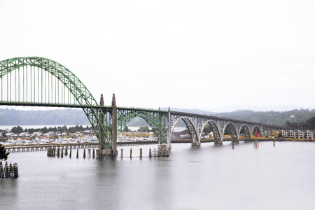 shores: Long arched bridge with sectional arches of different diameters and metal trusses and concrete pillars supporting the bridge connecting the two shores of the bay of the Pacific Ocean in Newport Oregon, where there are yachts and motor boats.