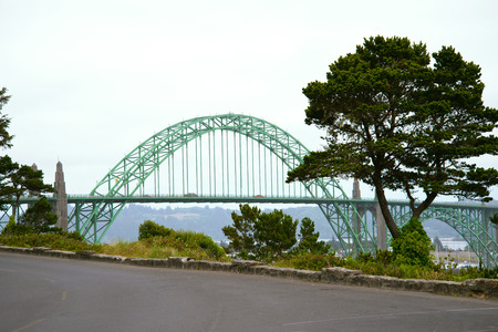 shores: Metal and concrete arch bridge with sectional arches and trusses connecting the two shores of the bay of the Pacific Ocean in Newport Oregon, amid growing trees with elegant crown. Stock Photo