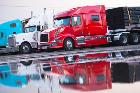 semitruck: Several big rig semi trucks of different models and colors of modern and classic red and white with a trailer in the parking lot with a load in anticipation of unloading reflected in the water on the pavement after the rain.