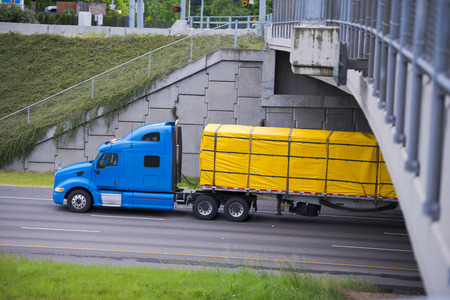 Profile of rapid powerful modern blue semi truck with a flat bed trailer 스톡 콘텐츠