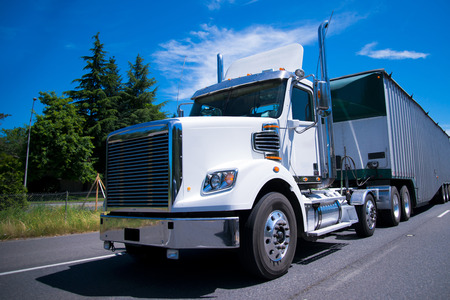 Contemporary modern and comfortable white big rig semi truck with day cab for local cargo freights