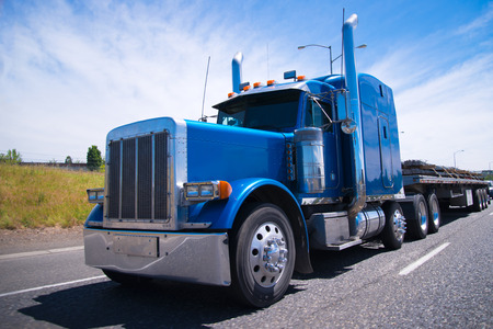 truck on highway: Classic blue bonneted big rig semi truck with chrome accessories