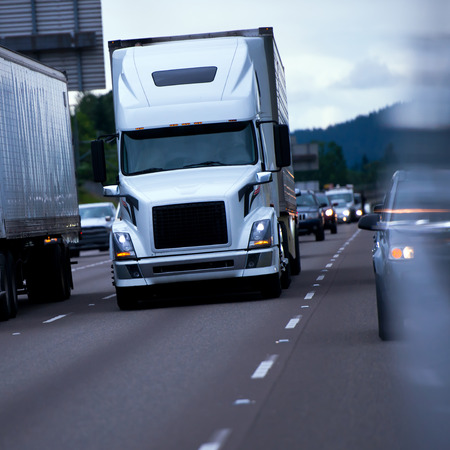 混雑、高速道路のヘッドライトで夜の真ん中に近代的な大きなリグ半トラック