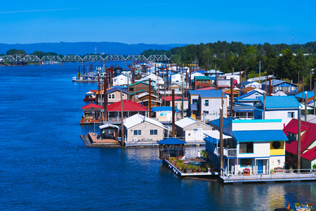 constitute: Bright multi-colored fancy houses standing on the pontoons on the water on the Columbia River constitute a floating residential area for lovers of life on the water in close proximity to nature.