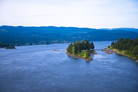 river: Green island covered with trees on the Columbia River  Stock Photo