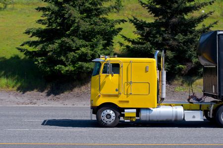 bonnet: Old bright yellow retro of previous years model semi truck without bonnet with a black trailer