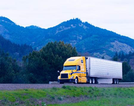 remolque: Populares poderosa amarilla gran plataforma de camión semi Moderno Foto de archivo