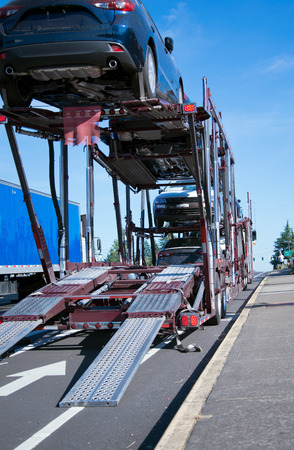2 단계 트레일러에서 자동차로 운송하는 세미 트럭 차량 운반 차량이 하역 용 도로에 있습니다.