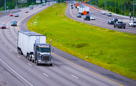 highway traffic: A broad highway with a dividing strip of grass opposite sides with a classic semi truck traffic and bulk trailer in the foreground. Stock Photo