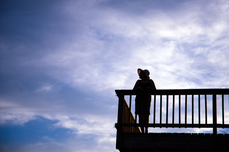 glorification: Silhouette of a woman in a hat with a beautiful figure leaned against the balcony