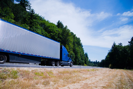 The modern model of the blue big rig semi truck with aluminum fluted corrugated refrigerator trailer speeding on a scenic green trees highway in the horizon, leaving a bend of the road.