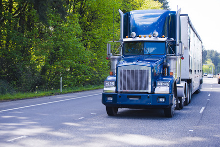 Dark blue classic popular semi truck with chrome details and a bulk trailer