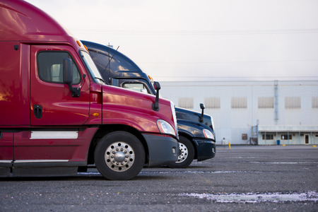 land transport: Two semi trucks of different colors stand in a row at the parking area in anticipation of the start of loading - unloading operations. Colorful profiles of cabins modern semi trucks. Stock Photo