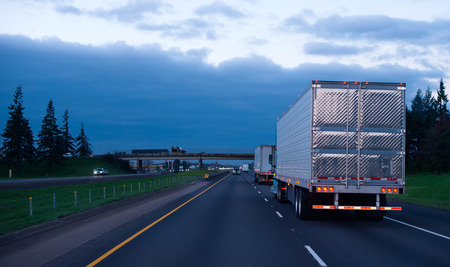 The convoy of semi trucks with reefer trailers on flat like an arrow evening road
