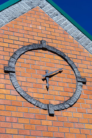 glorification: These stylized operating clock with arrows in a circle lined with stone blocks on the front wall