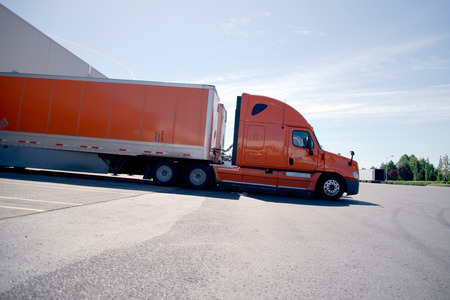 Stylish bright orange semi truck and dry van trailer were stretched for unloading at the warehouse at the site on a sunny day, the light casts a dense shade underneath the semi truck and trailer.