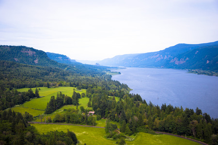 greatness: The greatness of nature and its Creator in a breathtaking panorama of the beautiful expanses Columbia Gorge with the waters of the Columbia River and mountainous coast with cultivated green fields, trees and a blue haze of infinite space. Stock Photo