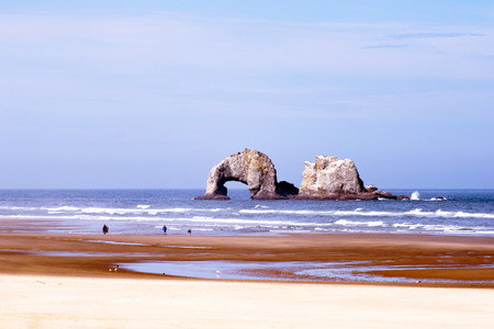 vastness: Two rocks ocean waves planed stick out of the water on a beautiful quiet sandy shores of the Pacific Ocean