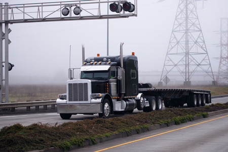 Stylish classic semi truck with chrome body trim and a flat bed trailer on the road with the traffic separation