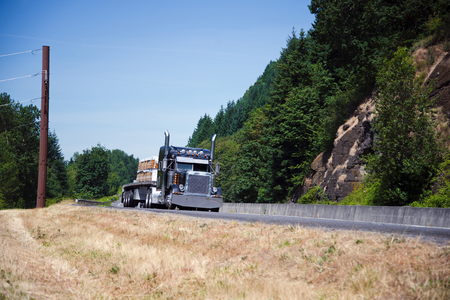 Powerful spectacular professional commercial classic dark blue semi - truck with an open trailer flat bed and chrome accents transports building boards on the highway near the picturesque cliffs covered with green trees. Foto de archivo