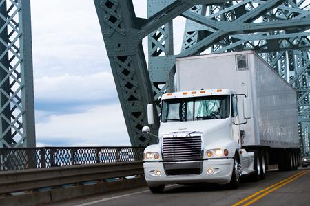 remolque: Blanca gran camión semi comercial con un remolque transporte de cargas industriales comerciales en movimiento en la carretera que pasa sobre el puente con poderosas estructuras de celosía de metales pesados ??y puente de reflexión en las partes brillantes del camión semi.