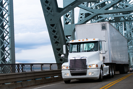 White large commercial semi truck with a trailer carrying commercial industrial loads moving on the highway passing over the bridge with powerful heavy metal truss structures and bridge reflection on the shiny parts of the semi truck.