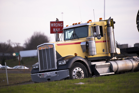 wrong way: Large popular classic semi - truck with chrome accents on highway exit with sign wrong way. The truck is tilted forward in the plane of inclination of the road and lit by the rays of the setting sun.
