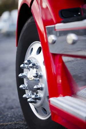 The powerful front wheel on the steering axle of the truck on a powerful modern aluminum wheels with chrome mounting bolts. Detail of a red truck with a wing and chrome complements the steps of the magnitude of this giant. Archivio Fotografico