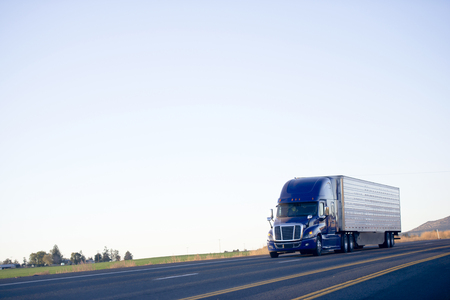 camion: Modernos enormes conductores poderosos populares aparejo grande semi-camión azul oscuro con un compartimiento para dormir y una periferia en una superficie plana de la carretera Carretera en la silueta contra el cielo monocromo.