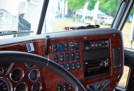 semi truck: Modern ergonomic and stylish dashboard of heavy semi truck with lots of equipment, indicators, buttons, and other electronics, decorated with plastic imitation wood, integrated into the interior of a large commercial truck cab.