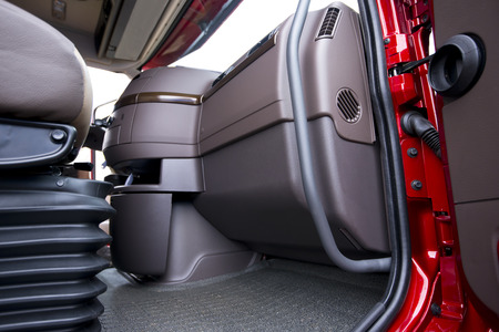 semitruck: The interior of a modern luxury red semi truck made in shades of brown plastic, metal and rubber. Through the open truck door visible part of the seat with shock absorbers and the dash console with air vents. Stock Photo