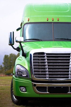 Wet from the rain stylish modern powerful green big rig semi truck with the latest model of commercial long-distance transport in the parking lot waiting for work on highway.