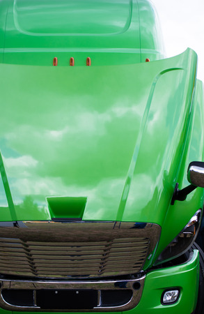 freightliner: Huge powerful light green modern sparkling of originality and purity big rig semi - truck with an open hood with chrome grille and fog lamps on the bamper that reflects the clouds.