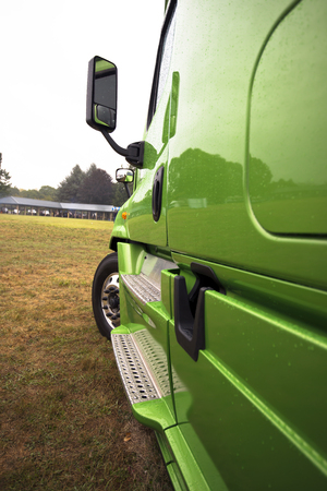 Side modern green semi truck with a shiny reflective paint everything as in a mirror with aluminum footrest, a mirror and a wheel on the grass parking lot with a view in perspective to the horizon.