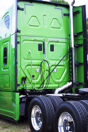 axle: A big green modern rig semi truck with a high cabin with flat rear wall, a fifth wheel and two axle with new tires on lightweight aluminum rims.