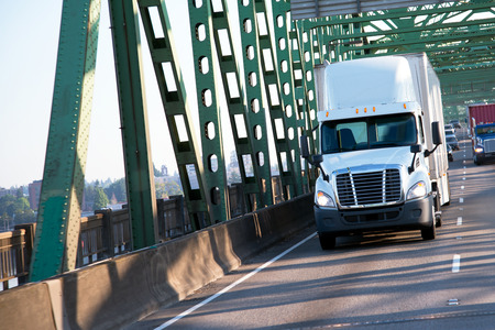 Modern white semi-truck with an aerodynamic spoiler and a covered trailer transporting commercial cargo on a divided highway bridge over the Columbia River on road with other cars, participates in the regular driving on the interstate highway.