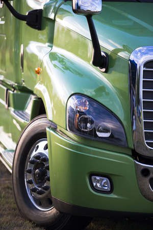 Sunlit powerful modern stylish and comfortable green big rig semi truck the latest model of commercial long-distance transport with shiny chrome grille in the parking lot waiting for cargo.