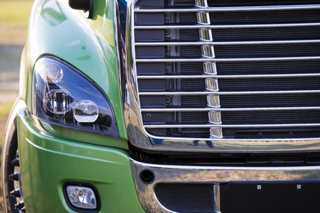 Sunlit powerful modern stylish and comfortable green big rig semi truck of latest model of commercial long-distance transport with shiny chrome grille and efficient headlight in the parking lot waiting for cargo.