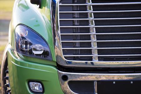 ciężarówka: Nasłonecznione potężne nowoczesne stylowe i wygodne zielony big rig semi truck najnowszego modelu komercyjnego transportu dalekobieżnego z błyszczącą chromowaną kratką i efektywnego reflektora na parkingu czekając na ładunek. Zdjęcie Seryjne
